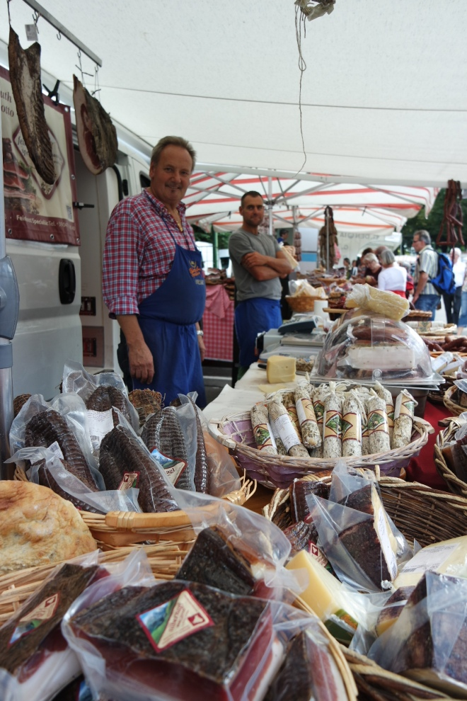 The market in Merano is stuffed full with food, clothes and people.